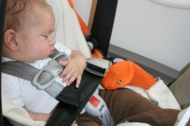 Bebê viajando de avião dentro de sua cadeirinha