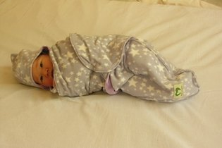 Enrolar bebê na manta e deitar de lado
